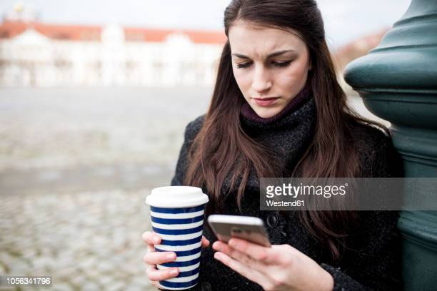 portrait of serious young woman with coffee to go leaning against lamp pole looking at cell phone - displeased ストックフォトと画像