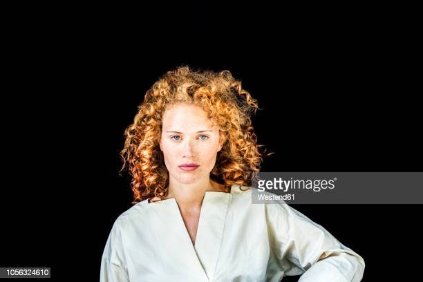 portrait of serious young woman with curly red hair in front of black background - curly stock pictures, royalty-free photos & images