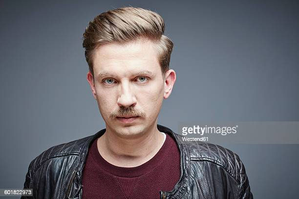 Portrait of seriuos looking man with moustache in front of grey background