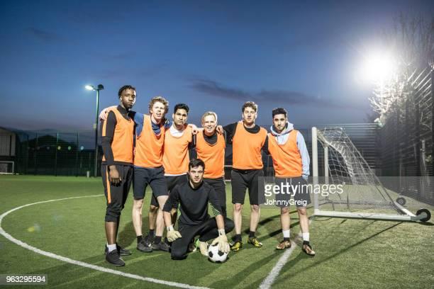 retrato de siete un fútbol equipo en cancha con los brazos alrededor de la otra - equipo de fútbol fotografías e imágenes de stock