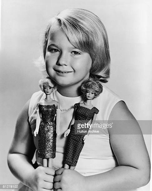 Portrait of sevenyearold Becky Ray the 400000th member of the Barbie Doll Fan Club as she poses with two 'Bubblecut' Barbie dolls each wearing a...
