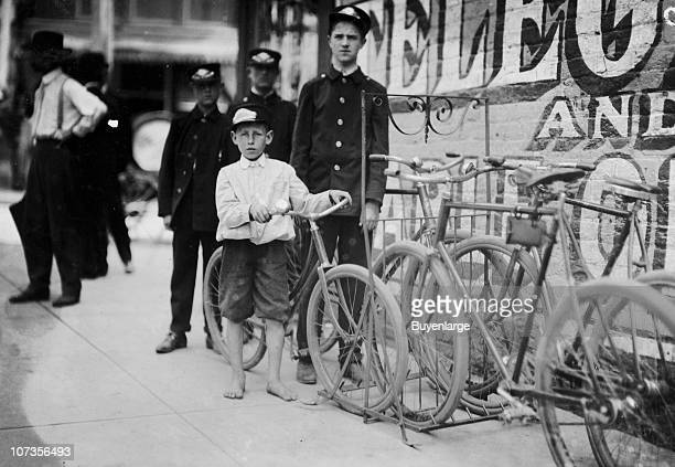 Portrait of several Western Union messengers as they pose next to a rack of bicycles Danville Virginia 1911 The youngest is ten years old and he is...