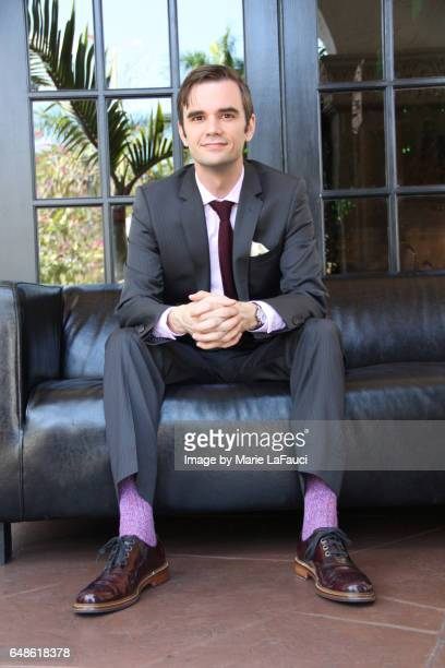 portrait of sharp-dressed man sitting on leather sofa - purple shoe stock pictures, royalty-free photos & images