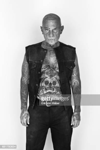 Portrait of shaven headed older man with tattoos