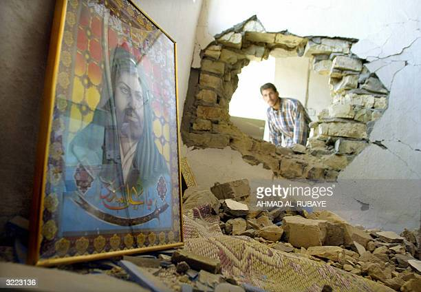 A portrait of Shiite Muslim Imam Ali lies 06 April 2004 against a wall in a damaged house as a man collects his belongings in Baghdad's Shiite...