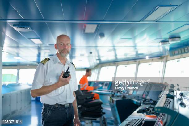 portrait of ship's captain on bridge onboard ship in port - team captain stock pictures, royalty-free photos & images