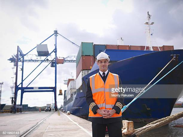 Portrait of ships captain standing in front of container ship