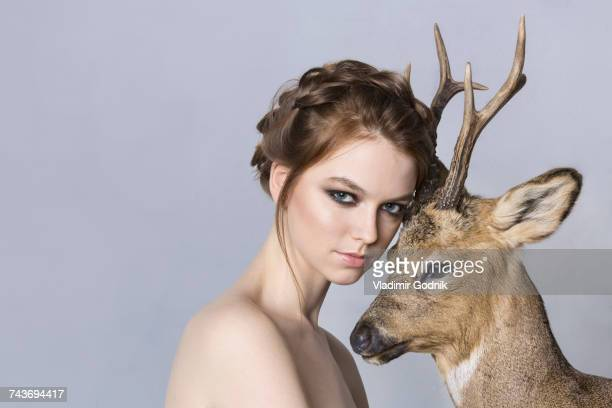 Portrait of shirtless beautiful woman with deer against purple background