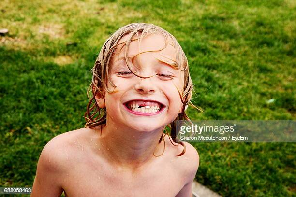 Portrait Of Shirtless Boy Showing Gap Toothed