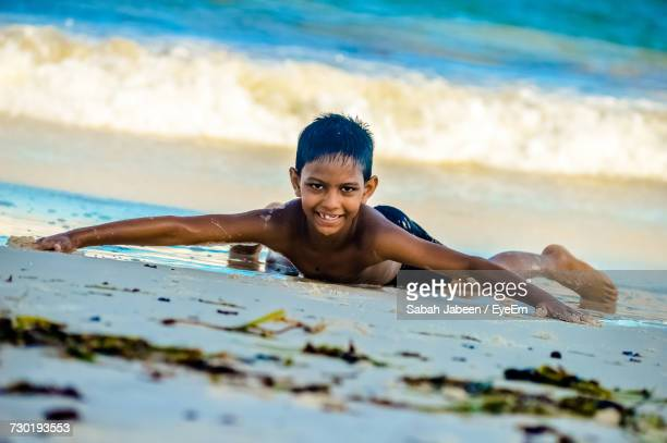 Portrait Of Shirtless Boy Smiling While Lying At Beach