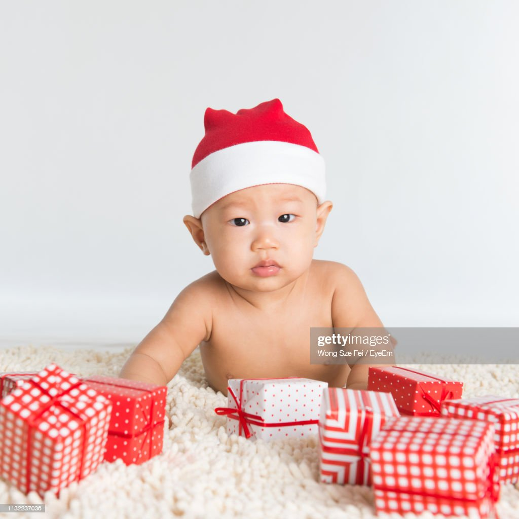 889fd3d51 Portrait Of Shirtless Cute Baby Boy Wearing Santa Hat With Christmas ...