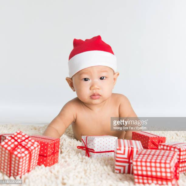 869a7116aa87 Portrait Of Shirtless Cute Baby Boy Wearing Santa Hat With Christmas  Presents Lying On Rug Against