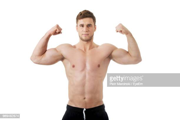 portrait of shirtless man flexing muscles against white background - shirtless stock pictures, royalty-free photos & images