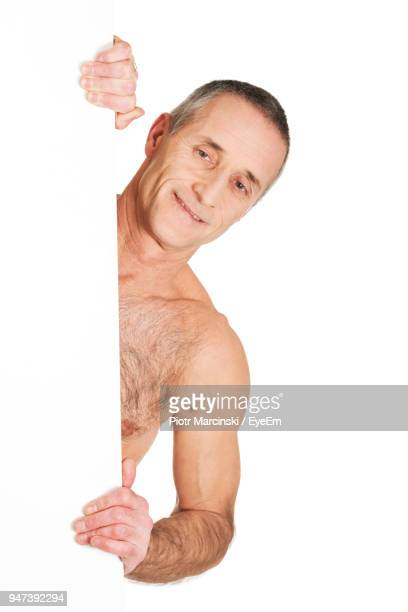 Portrait Of Shirtless Man Holding Placard Against White Background