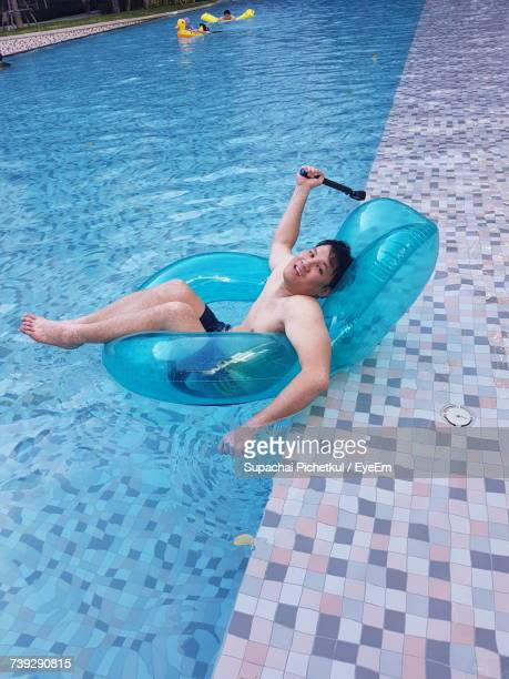 Portrait Of Shirtless Man Lying On Inflatable Chair In Swimming Pool