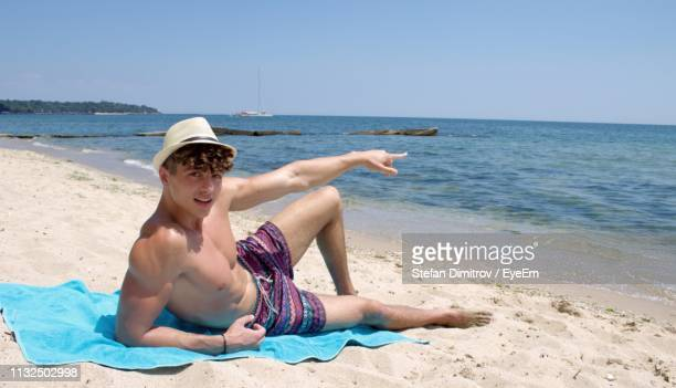 portrait of shirtless man pointing while relaxing at beach against clear sky - dimitrov - fotografias e filmes do acervo