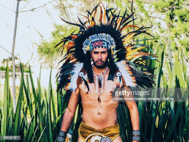 Portrait Of Shirtless Man Wearing Apache Headdress While Standing Against Plants