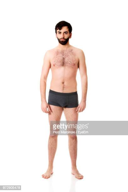portrait of shirtless man wearing underwear against white background - shirtless stock pictures, royalty-free photos & images