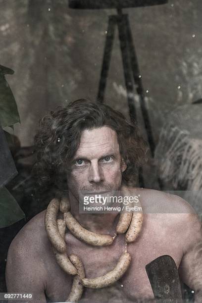 Portrait Of Shirtless Man With Sausages Around Neck