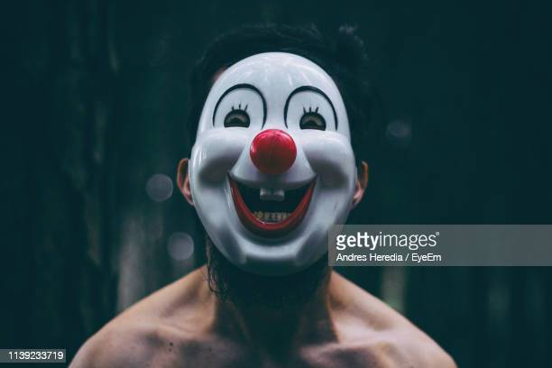 portrait of shirtless mid adult man wearing clown mask while standing outdoors - clown stock-fotos und bilder