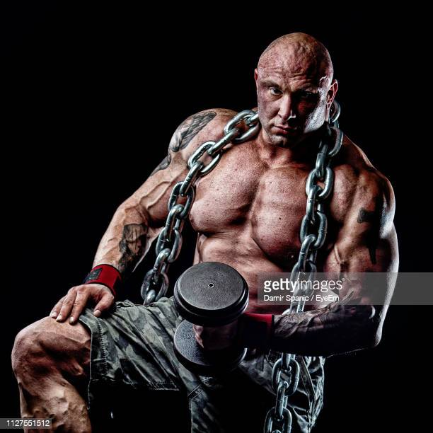 portrait of shirtless muscular man lifting dumbbell against black background - bodybuilding stock-fotos und bilder