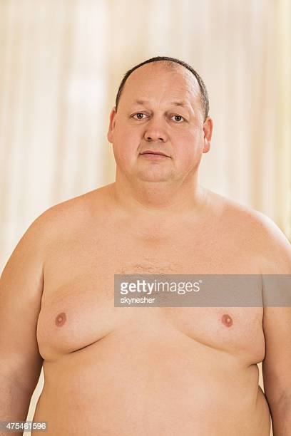 Portrait of shirtless overweight man looking at camera.