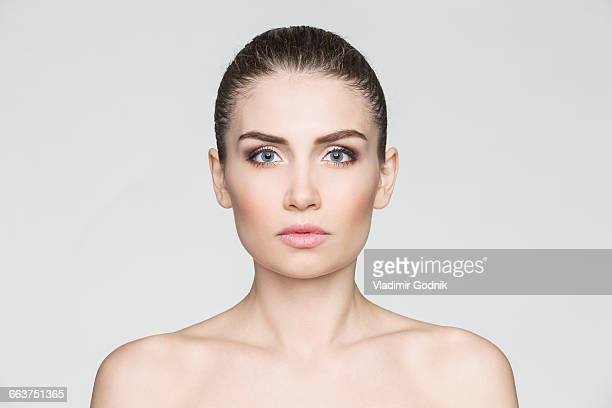 Portrait of shirtless woman against white background