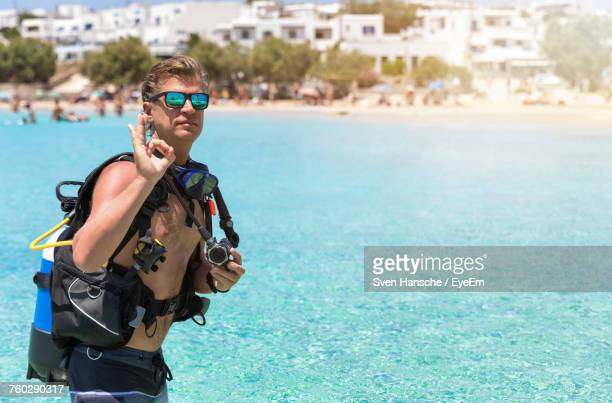 portrait of shirtless young man wearing sunglasses showing ok sign while standing at beach - ver a hora stockfoto's en -beelden