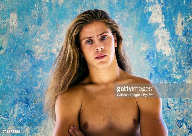 portrait of shirtless young man with long hair standing against blue wall - lang haar stockfoto's en -beelden