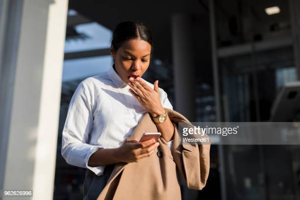 Portrait of shocked businesswoman reading email on her mobile phone
