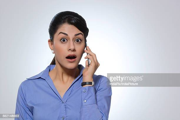 Portrait of shocked businesswoman using mobile phone against gray background