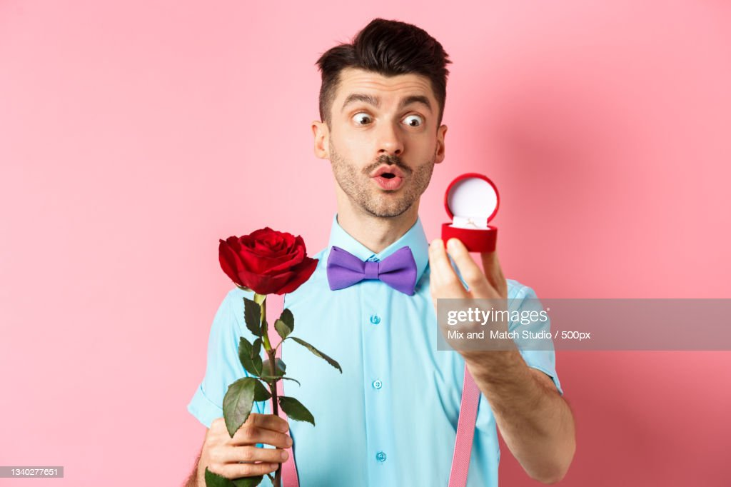 Portrait Of Shocked Man Holding Red Rose Against Red ...