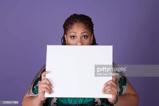 portrait of shocked woman holding blank placard while standing against purple background - person holding up sign stock pictures, royalty-free photos & images