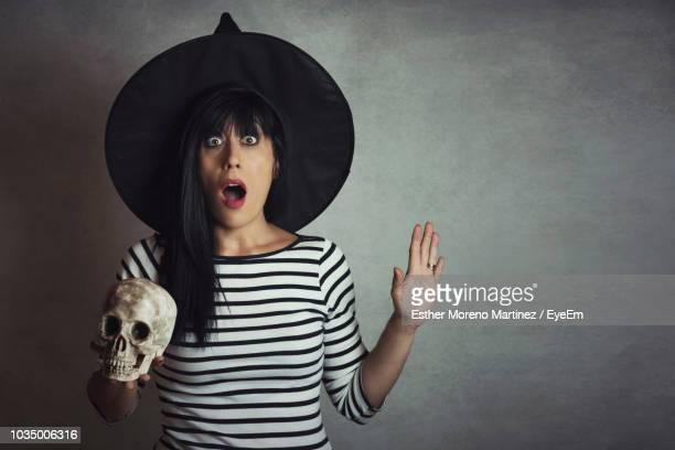 Portrait Of Shocked Woman Holding Skeleton While Standing Against Gray Wall