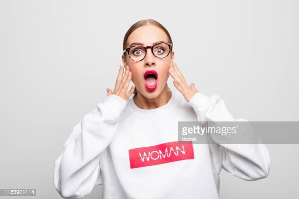 portret van geschokte vrouw in wit t-shirt - izusek stockfoto's en -beelden