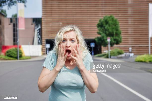 Portrait of shocked woman outdoors