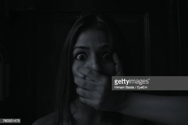 Portrait Of Shocked Woman With Mouth Covered By Hand In Darkroom