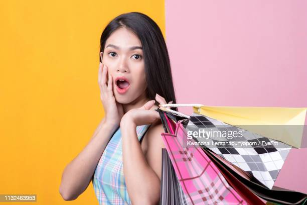 portrait of shocked woman with shopping bags standing against colored background - ツートンカラー ストックフォトと画像