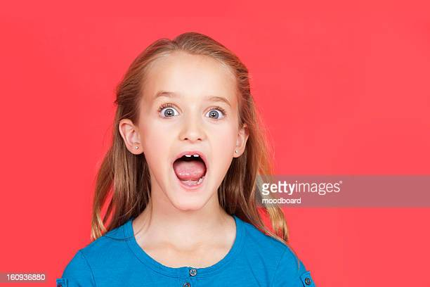 Portrait of shocked young girl with mouth open against red background