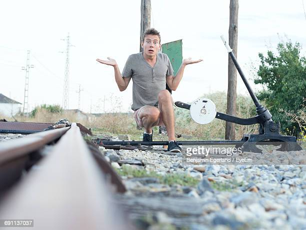Portrait Of Shocked Young Man Crouching By Railroad Switch Stand