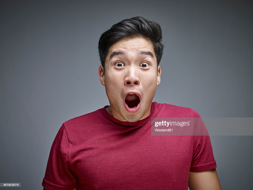 Portrait of shocked young man in front of grey background : Stock-Foto