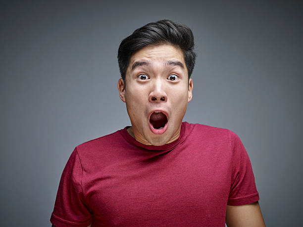 portrait of shocked young man in front of grey background - shocked asian man stock pictures, royalty-free photos & images