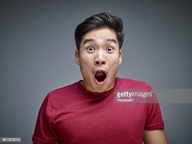 portrait of shocked young man in front of grey background - surpresa - fotografias e filmes do acervo