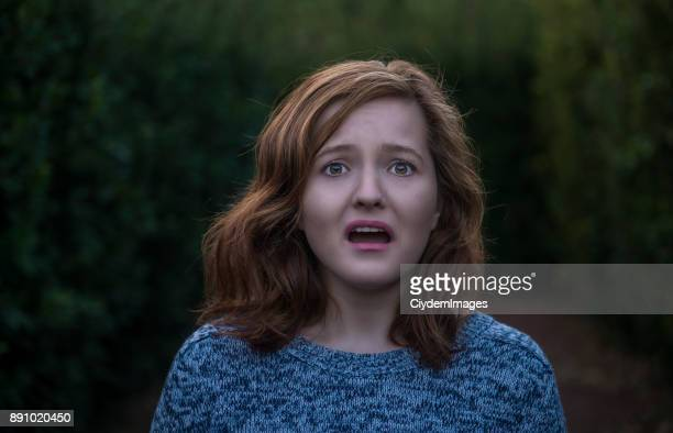 portrait of shocked young woman looking at camera with negative facial expression - scary face stock photos and pictures