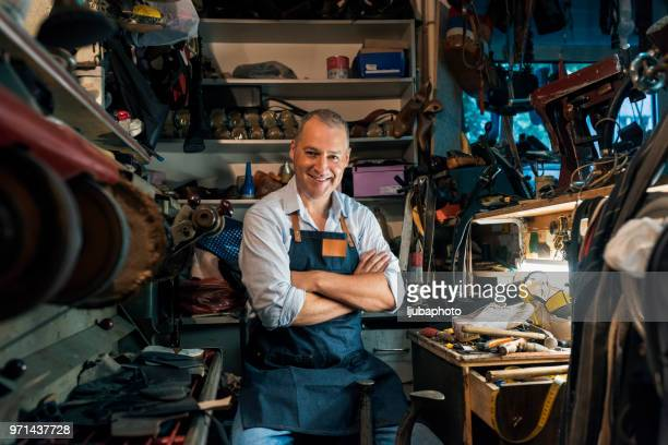 portrait of shoemaker sitting with arms crossed in workshop - leather shoe stock pictures, royalty-free photos & images