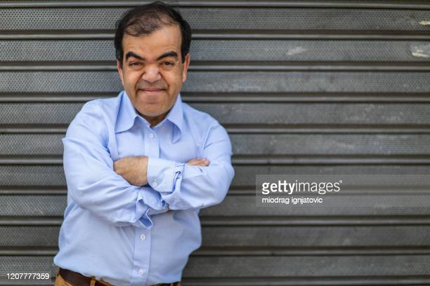 portrait of short man standing in front of rolling garage door - dwarf man stock pictures, royalty-free photos & images
