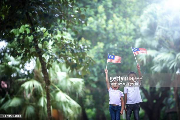 portrait of siblings holding malaysian flag while standing against trees at park - happy flag day stock pictures, royalty-free photos & images