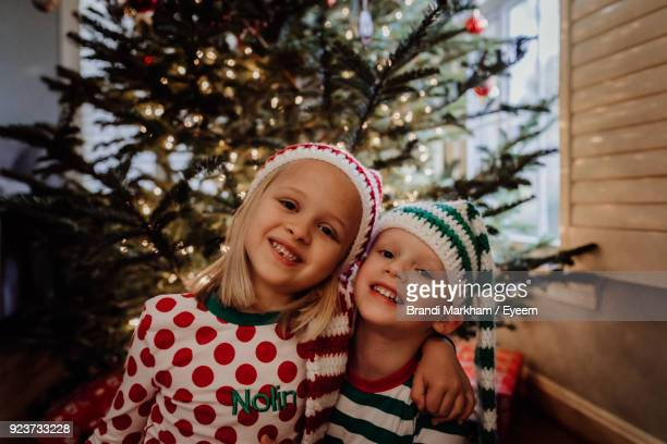 portrait of siblings in costume sitting against christmas tree at home - brandi love photos et images de collection