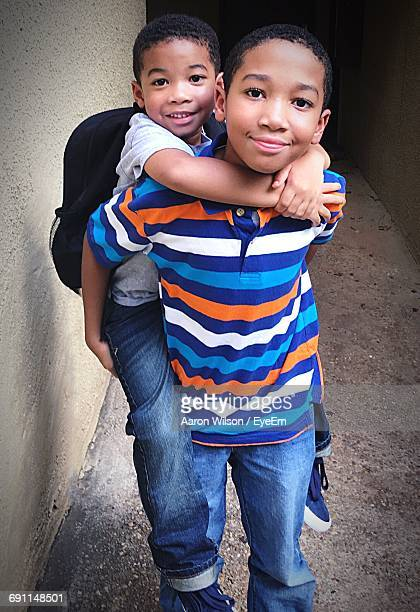 Portrait Of Siblings Piggybacking In Alley