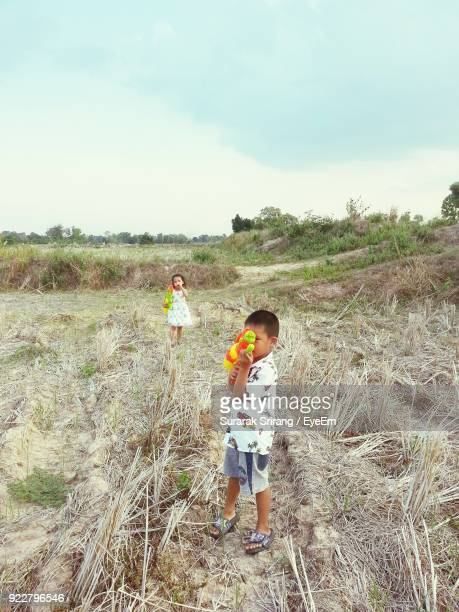Portrait Of Siblings Playing With Squirt Guns While Standing On Field